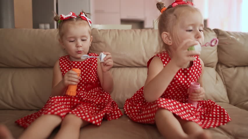 Two little twin sisters in charming red dresses are blowing soap bubbles cheerfully while sitting in the room barefoot. | Shutterstock HD Video #25481411