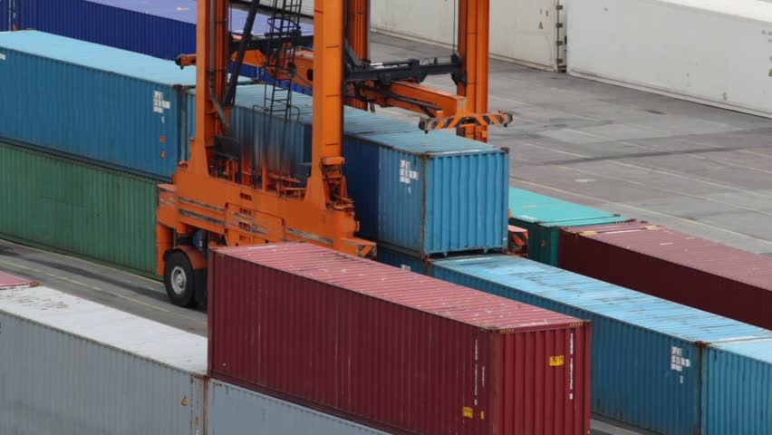 Reachstacker lifts one of several containers in port at day - HD stock footage clip