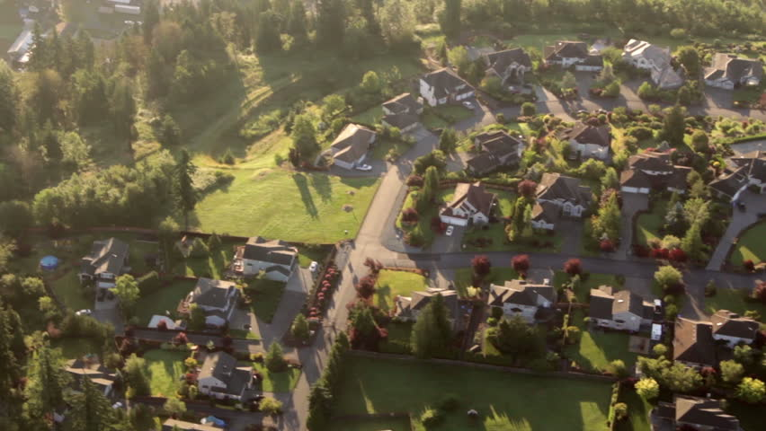 Aerial view from low-flying airplane of residential estates in wealthy neighborhood on a hill