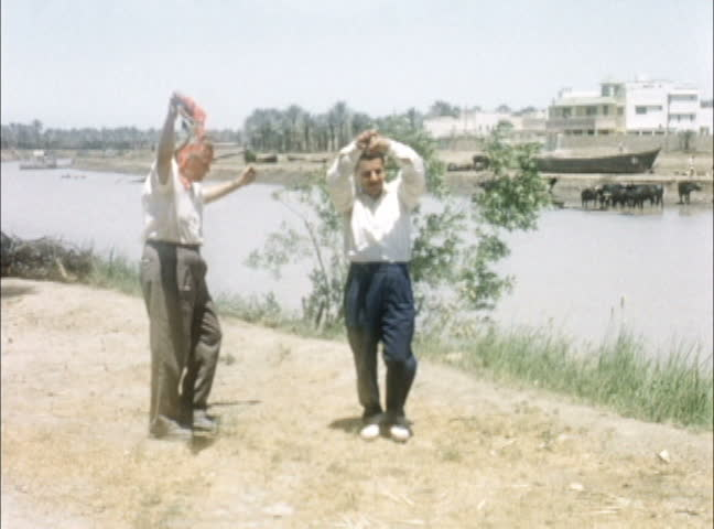 IRAQ - JULY 1956: American tourist dances with Iraqi guide along banks of the Euphrates, Iraq. Shot on 16mm film.