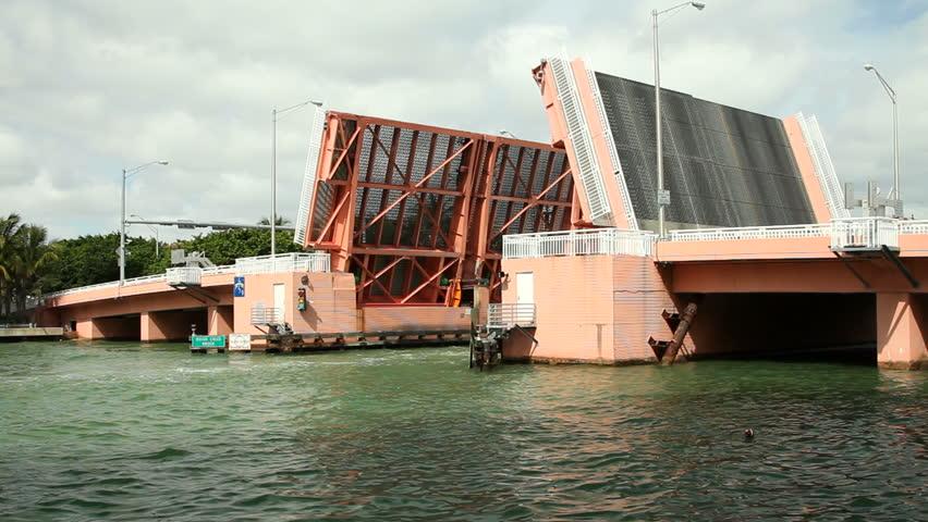 Beautiful luxury nautical vessel crossing under raised Indian Creek Bridge in Miami Beach, Florida - HD stock footage clip