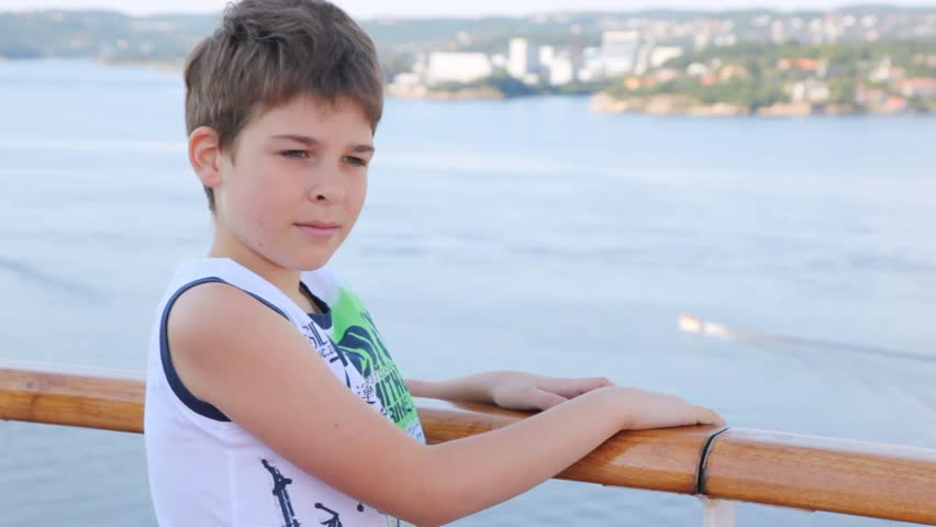 Boy stands on ship deck against sea and city in afternoon - HD stock footage clip