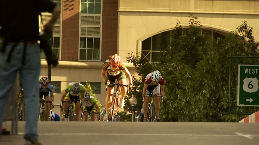 PROVIDENCE, RHODE ISLAND - SEPTEMBER 3, 2009: Woman bicycle racer winning race and celebrating as she crosses finish line- slow motion - HD stock footage clip