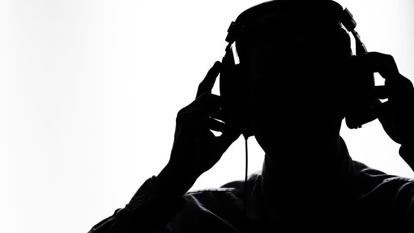 Man putting on headphones to jam. Silhouette. | Shutterstock HD Video #25750097