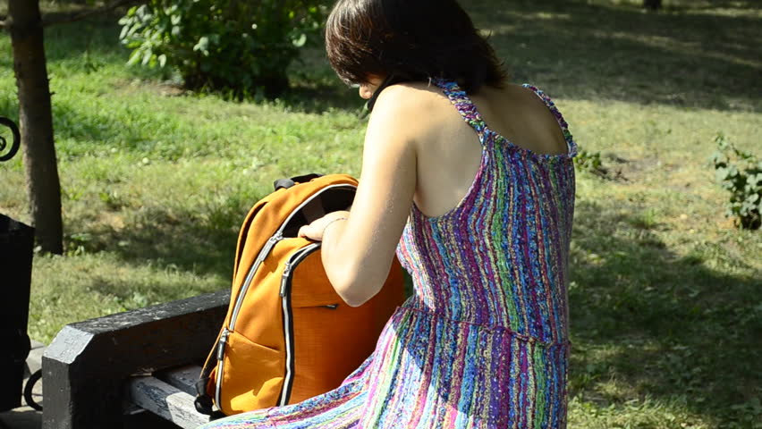 A young pregnant woman talking on the phone and digging in the backpack - HD stock footage clip