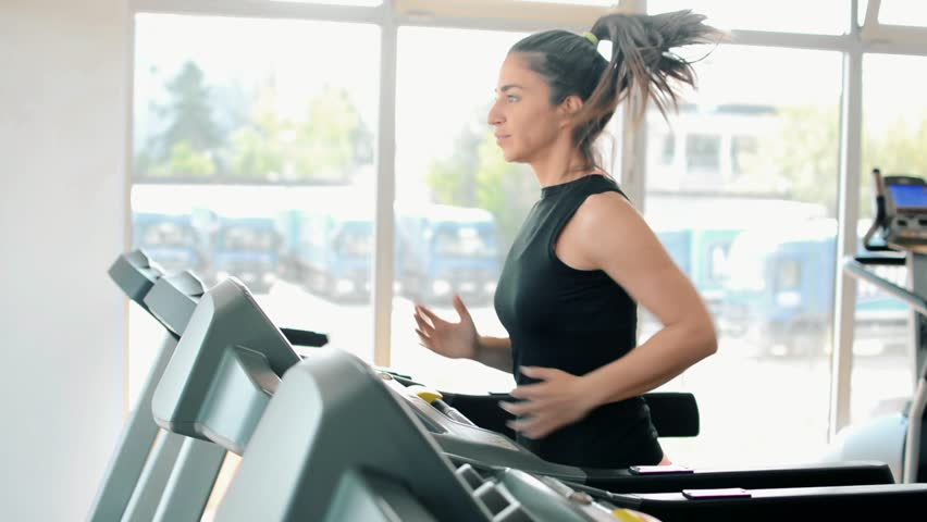 Sporty woman running on a treadmill in gym. Colorful lighting effects added on video. | Shutterstock HD Video #25898615