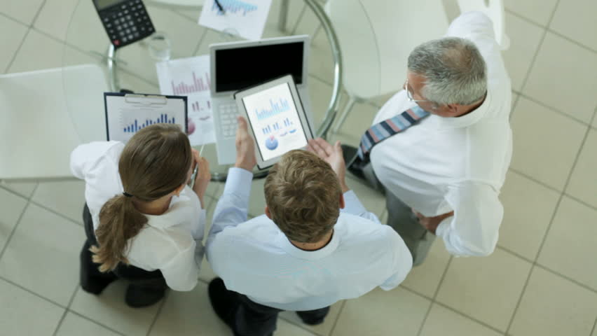 Business team of three comparing digital data and its hard copy during discussion