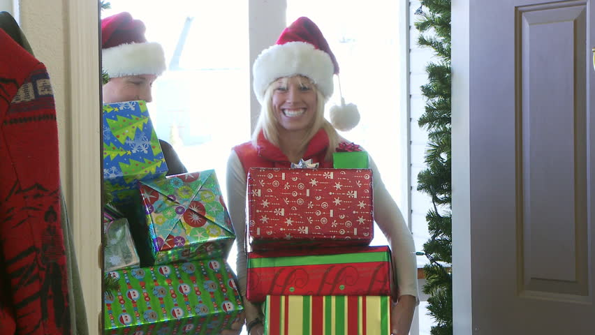 Couple in Santa Claus hats bringing presents and wrapping paper in through the front door - HD stock video clip