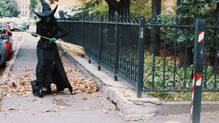 Cosplayer in halloween costume of green witch from The Wizard of Oz walking down autumn city street holding broom, get surprised and run away | Shutterstock HD Video #26065493