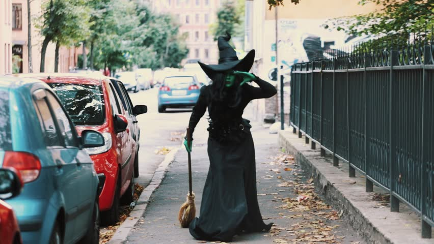 Cosplayer in halloween costume of green witch from The Wizard of Oz walking down autumn city street holding broom, look into distance and speed up | Shutterstock HD Video #26065556