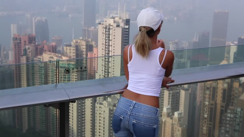 A sports American girl tourist is standing on the viewing platform of Victoria Peak in Hong Kong. She looks from above to the skyscrapers and the bay | Shutterstock HD Video #26079893
