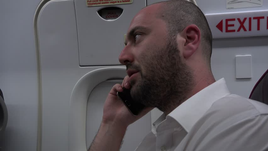Busy businessman business man airplane plane interior talking on mobile phone 4K | Shutterstock HD Video #26099036