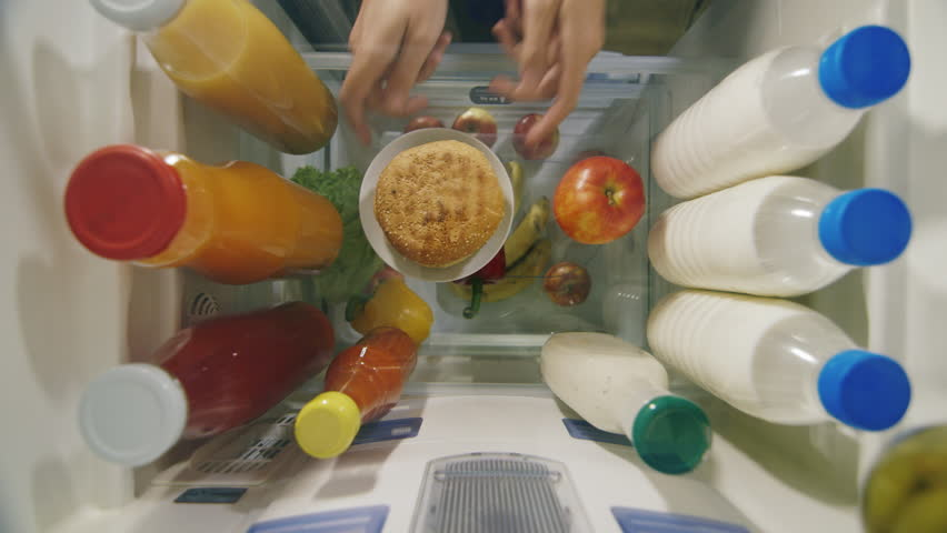 Choosing between healthy and unhealthy foods. The hand in the fridge takes the apple first, and then the fat burger. View from inside the refrigerator | Shutterstock HD Video #26121392