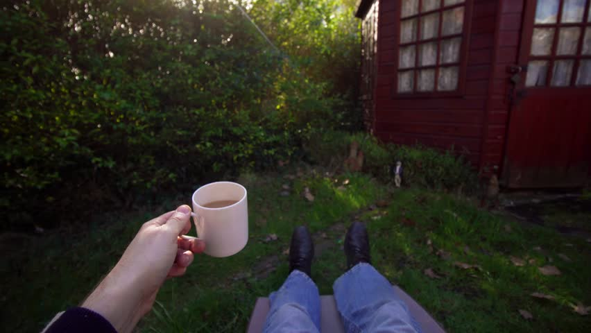 Caucasian white adult man relaxes outdoors on a sun lounger whilst drinking a cup of tea / coffee. Point of view POV shot on a sunny day in the garden. Time off, relaxing and enjoying outside sunshine | Shutterstock HD Video #26123075