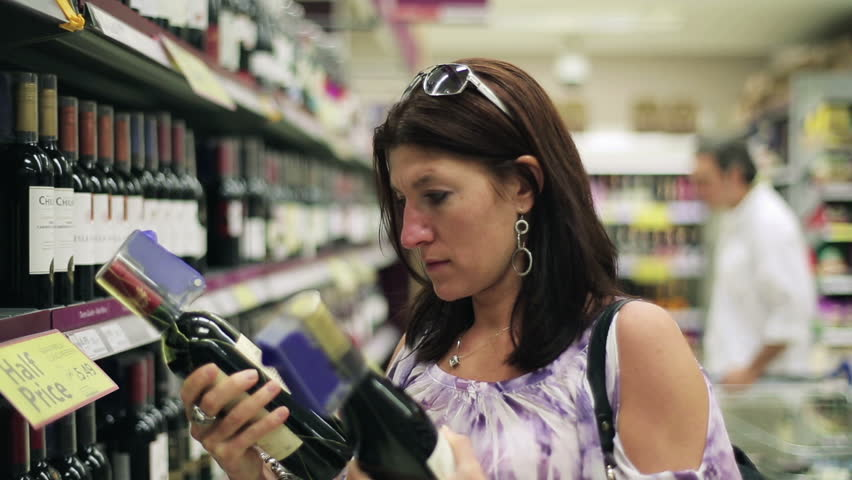 Young woman checking wine in supermarket,