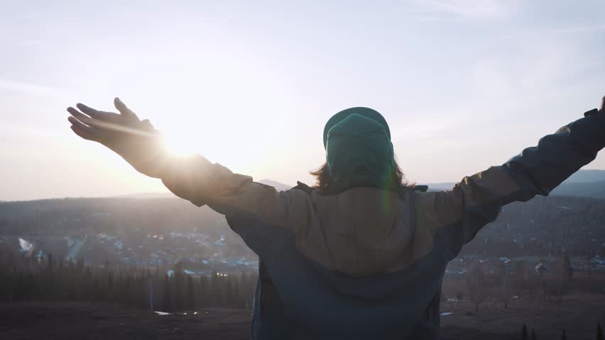 A young male traveler came to success. He throws his arms up, feels a sense of freedom. I reached the goal, I completed my journey. | Shutterstock HD Video #26197199