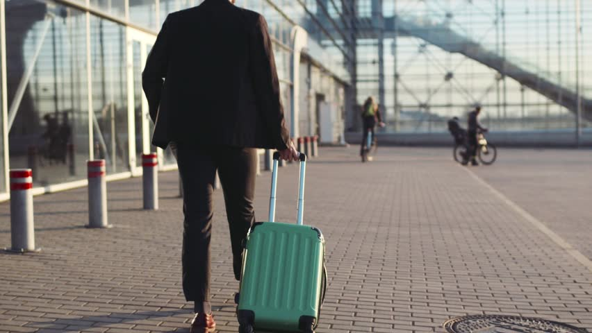 Young stylish bearded man in a suit walking to the airport, pulling suitcase and answering his phone call. Business style, active lifestyle. Traveling time. | Shutterstock HD Video #26209052