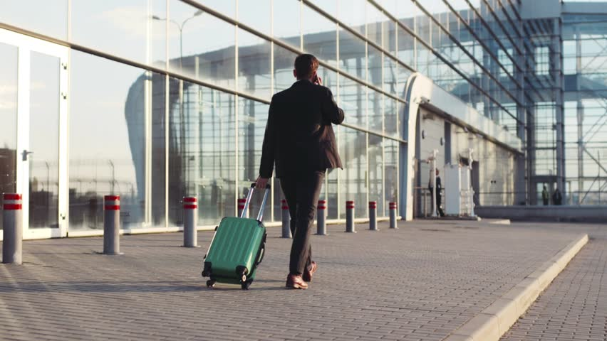 Stylish young bearded man talking on the phone while entering the airport terminal with luggage. Successful life. Business style, traveler, modern lifestyle. Active lifestyle. | Shutterstock HD Video #26209070