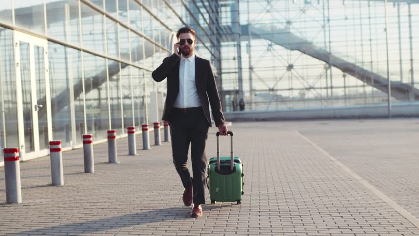 Stylish young bearded man in sunglasses exiting the airport terminal with luggage, talking on the phone. Business style, traveler, modern lifestyle. Active lifestyle. | Shutterstock HD Video #26209133