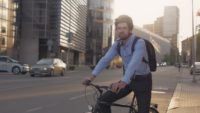 Happy commuter with his bike early in the morning. Portrait of handsome responsible office worker using eco-friendly transport in the city. | Shutterstock HD Video #26214965