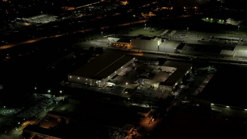 AERIAL HELI SHOT: Flying above illuminated with lights storage place, distribution center and storehouse at night. International logistic and depository center shipping, transporting warehousing goods | Shutterstock HD Video #26215010