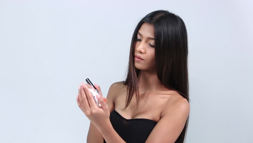Dark Tan Skin Woman Black Hair Fashion Make Up, holding presenting cosmetic brush and mirror case on face, studio gray background copy space for text logo | Shutterstock HD Video #26219609