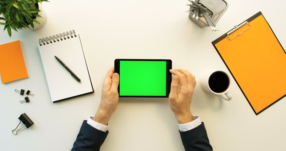 Business man using tablet device with green screen on white office desk with orange details. Male hand scrolling pages, zooming on tablet computer with green screen. Top view. Chroma key | Shutterstock HD Video #26225675