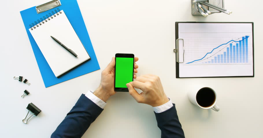 Business man using smart phone with green screen, scrolling pages, tapping on touch screen on office desk with financil charts, papers. Hands top view. Green screen. Chroma key | Shutterstock HD Video #26225756