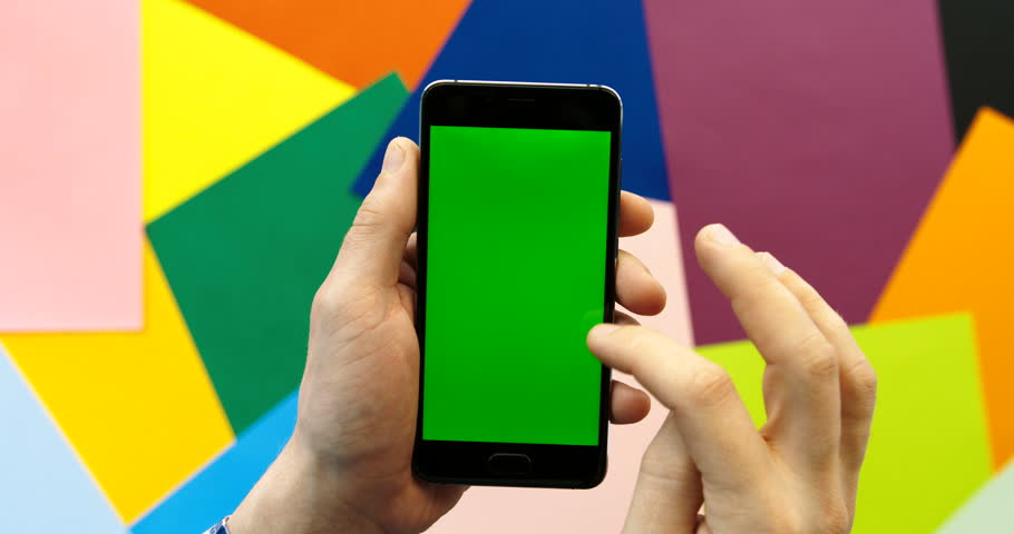 Man holding smart phone with green screen in colorful background. Man hands tapping and scrolling pages on cell phone with green screen. Chroma Key. Close up. Colorful paper background | Shutterstock HD Video #26225900