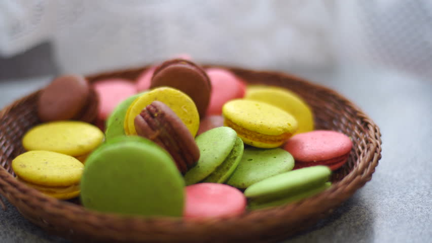 Girl puts a basket with colorful macaroon cookies on table close-up | Shutterstock HD Video #26232497
