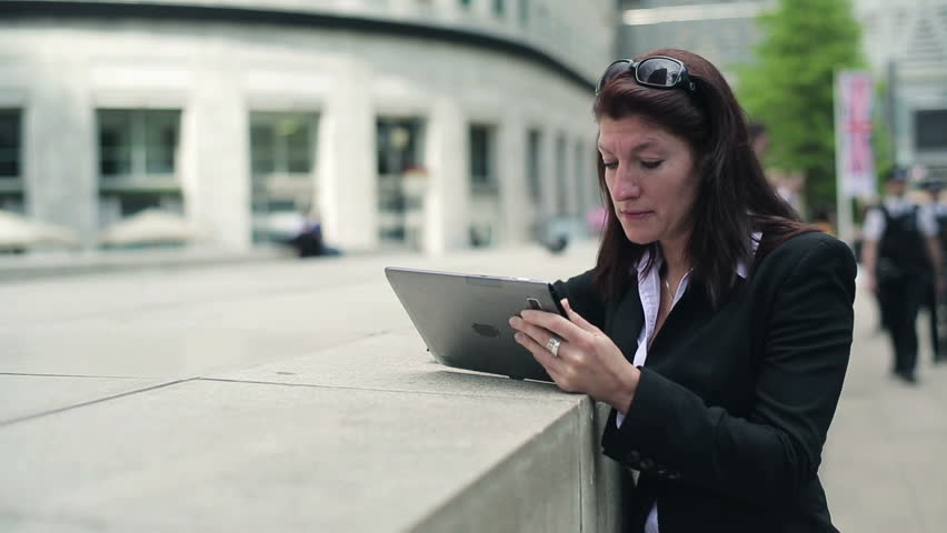 Young businesswoman reading bad news on tablet computer in the city  - HD stock footage clip
