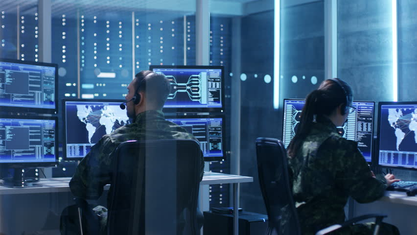 Male and Female Military IT Technicians Working on Computers with Multiple Displays Showing Various Information. Possible Surveillance, Army Maneuvers. Shot on RED EPIC-W 8K Helium Cinema Camera. | Shutterstock HD Video #26261540