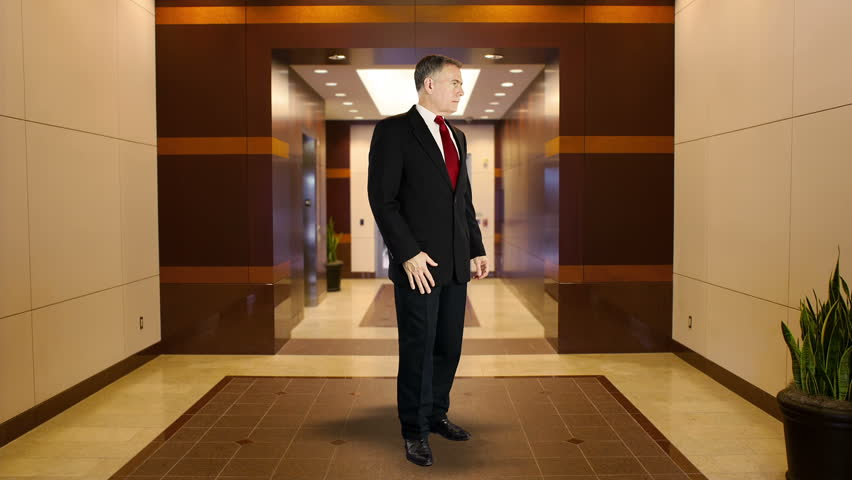 Mature businessman standing in middle of office building lobby area with confident smile and body language. - HD stock video clip
