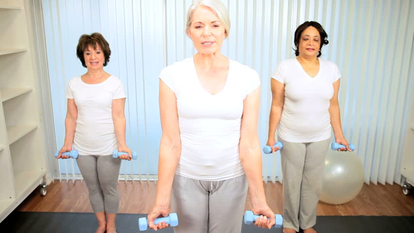 Mature Caucasian female instructor teaching muscle stretching with weights to senior ladies - HD stock video clip