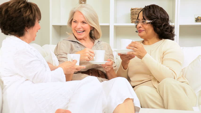Group older multi ethnic ladies laughing drinking coffee home - HD stock video clip
