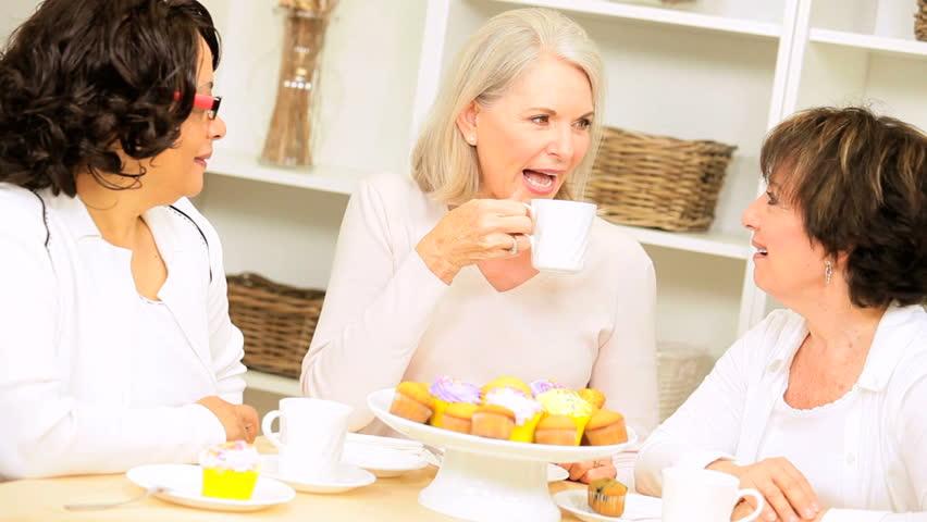 Three senior lady friends visiting drinking coffee enjoying tempting cakes home