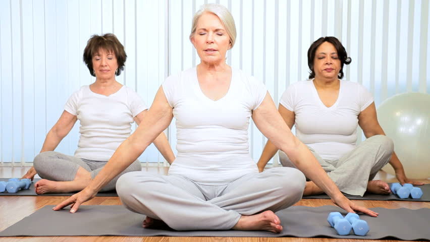 Three multi ethnic retired ladies exercising senior yoga class - HD stock video clip