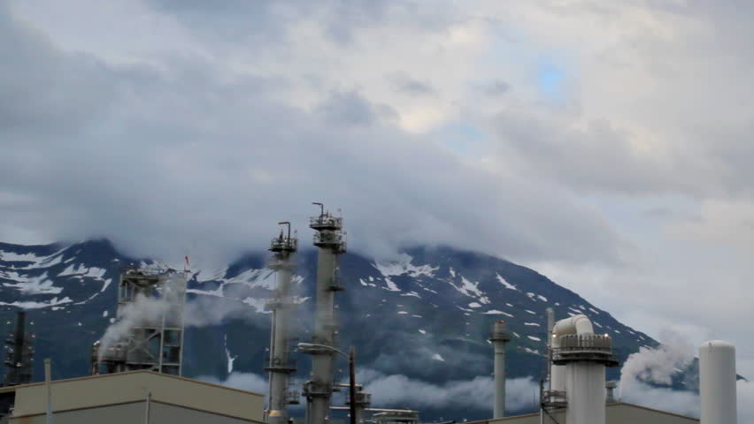 Oil Refinery in Valdez, Alaska in action with a bird flying by and fire and smoke coming out of the stacks on a cloudy day. - HD stock footage clip