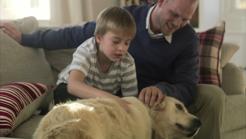 Father and son sitting in a sofa with a dog
