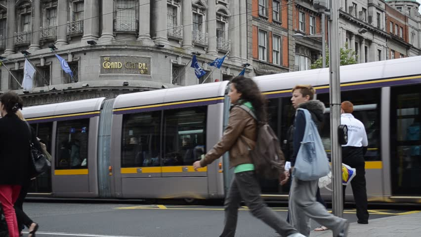 DUBLIN, IRELAND - CIRCA 2011: Public transport tram system (LUAS) and people crossing the intersection circa 2011 in downtown Dublin, Ireland.