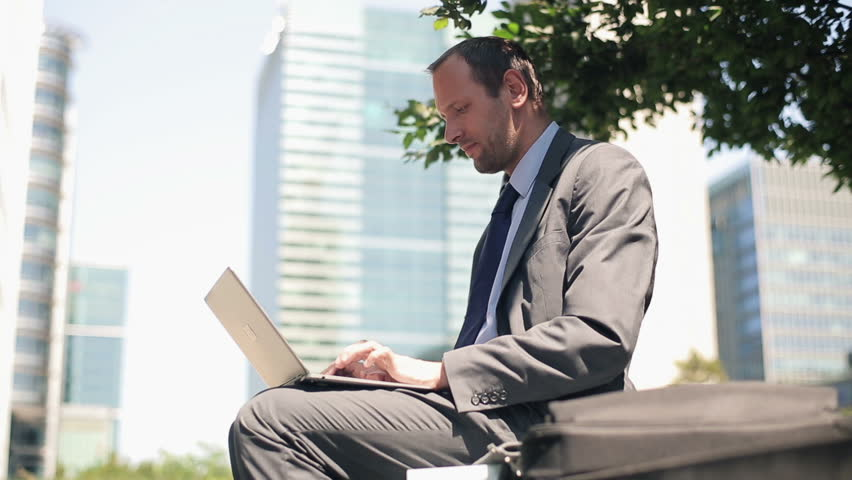 Businessman with laptop having a break and relaxing in the city