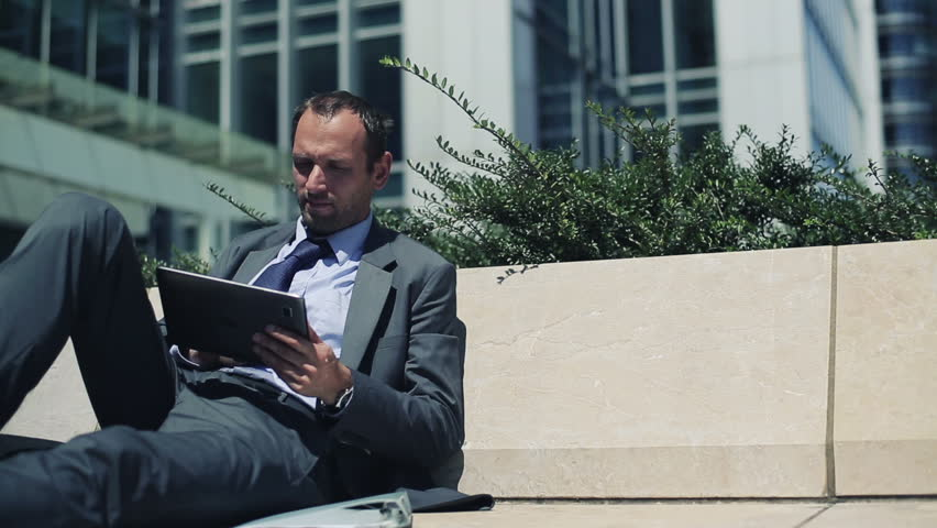 Businessman with tablet computer relaxing in the city