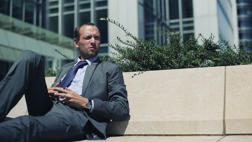 Happy young businessman having a break and relaxing in the city