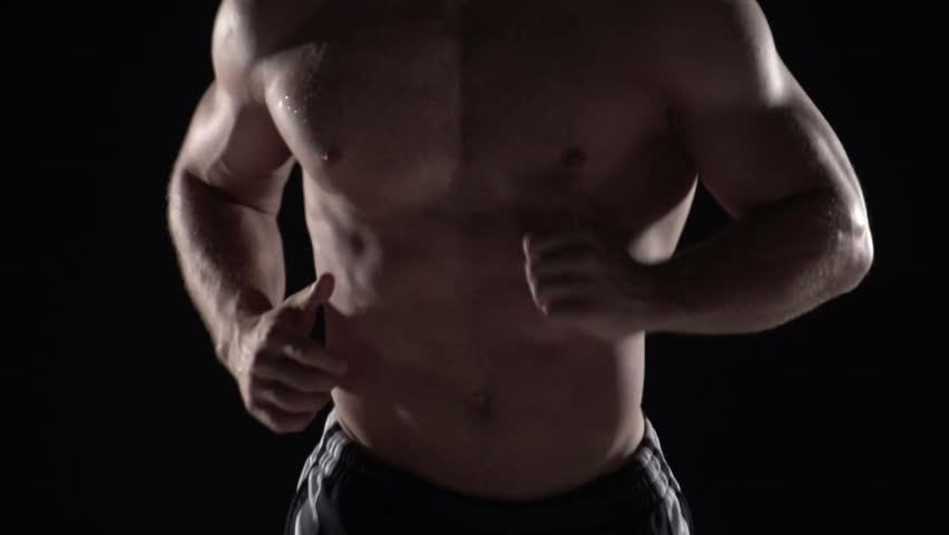 Muscular man running towards camera, torso shot center - HD stock video clip