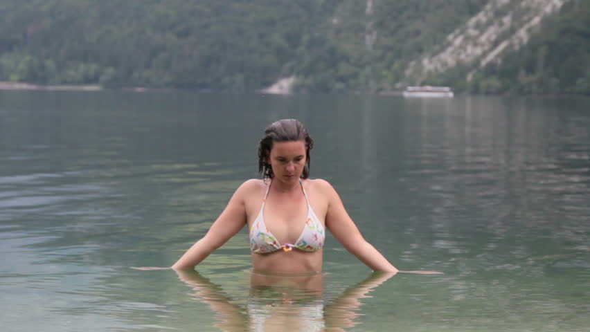 Cute girl splashing water in mountain lake - HD stock footage clip