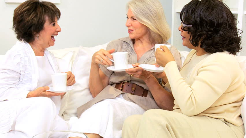 Three retired multi ethnic girlfriends visiting drinking coffee home - HD stock video clip