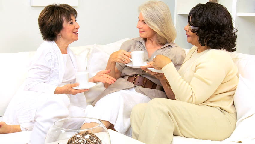 Three senior lady friends enjoying leisure drinking coffee home sofa - HD stock footage clip