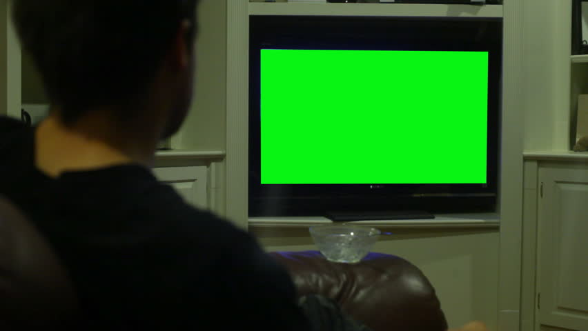 Watching TV, replaced screen with greenscreen - HD stock footage clip