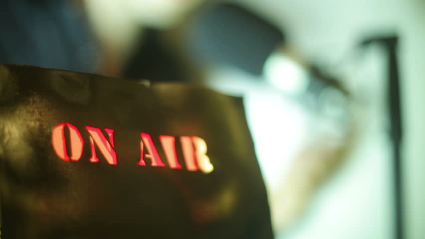 On air sign with a radio/tv announcer in the background - HD stock video clip