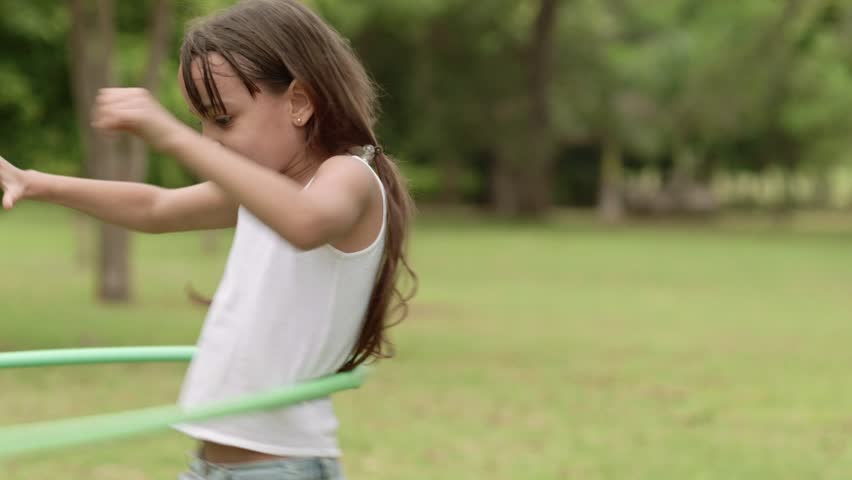 Children and toys, young girl having fun and playing with hula-hoop outdoors. Slow motion